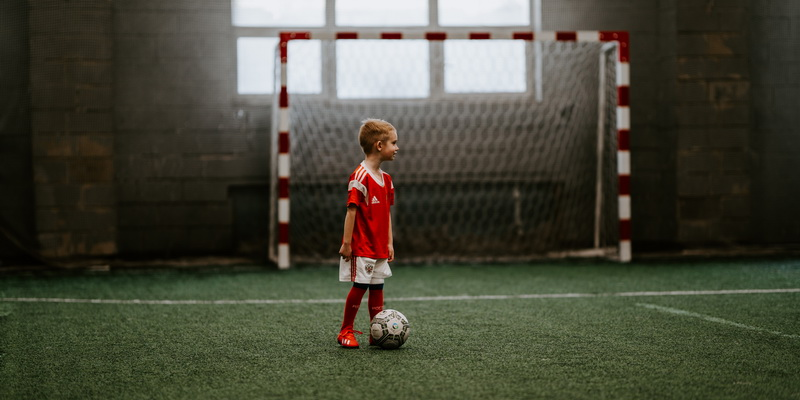 A child next to a soccer ball - football and soccer history facts